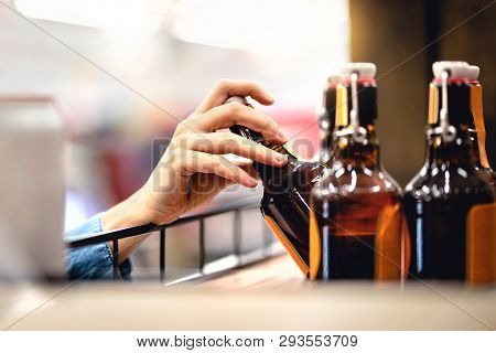 Hand Taking Bottle Of Beer From Shelf In Alcohol And Liquor Store. Customer Buying Cider Or Supermar