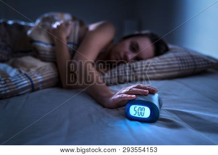 Tired woman waking up for work or school early in the morning. Grumpy lady pushing snooze button or turning off alarm clock with hand. Getting up after sleeping. Exhausted person in bed. Dark bedroom. poster
