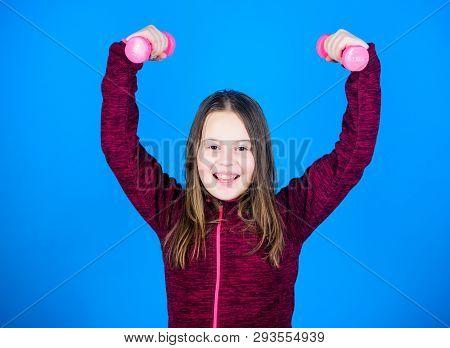 Toward stronger body. Rehabilitation concept. Girl exercising with dumbbell. Beginner dumbbell exercises. Child hold little dumbbell blue background. Sport for teens. Easy exercises with dumbbell poster