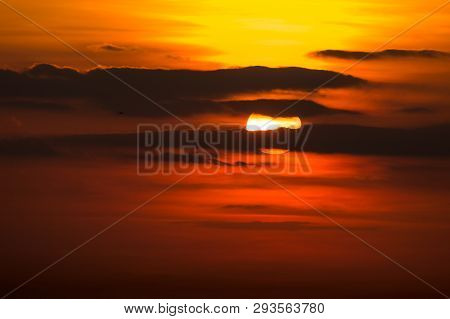 Dramatic Sunset In Red, Yellow And Orange With Clouds In The Sky