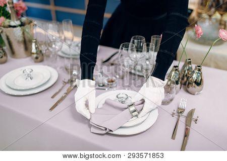 Waitress prepares tablecloth, table setting