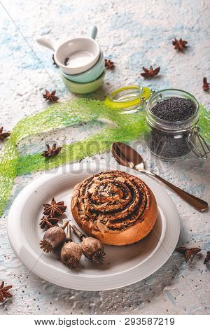 Sweet Rolled Bun With Poppy On White Plate With Few Poppyheads