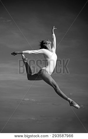 Grace In Every Move. Practicing Art Of Classical Ballet. Ballerina Jumping On Blue Sky. Cute Ballet