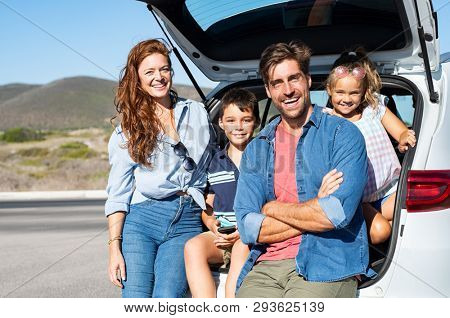 Smiling family with two kids sitting in car trunk and looking at camera. Happy children enjoying with mother and father a road trip while sitting in car back. Portrait of cheerful young family in auto