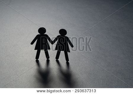 Paper figure of a female couple holding hands on gray surface. Same-sex marriage, diversity, minorities concept.