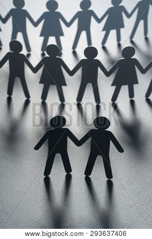 Black paper figure of a male couple in front of a crowd of paper people holding hands on white surface. Social movement, protest, leadership concept.