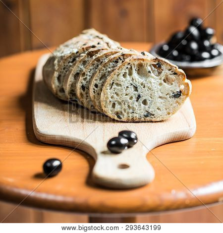 Slices Of Black Olive Bread On A Wooden Table
