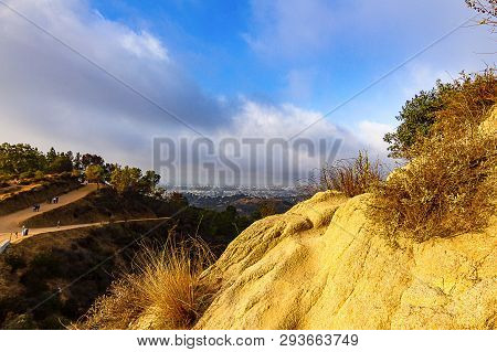Hillside View Of Hiking Trails And Distant City At Dawn