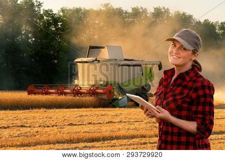 Woman Farmer Uses A Digital Tablet Control Autonomous Harvester. Smart Farming Concept