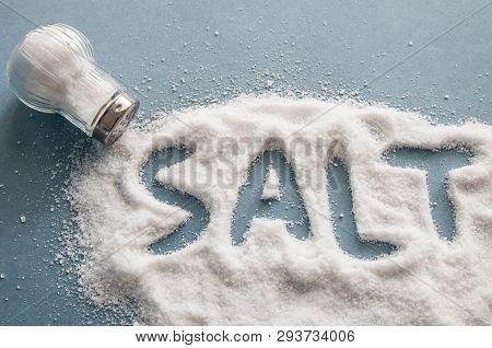 A Pile Of Salt From Salt Shaker, Word Salt, Concept Excessive Salt Intake And White Death