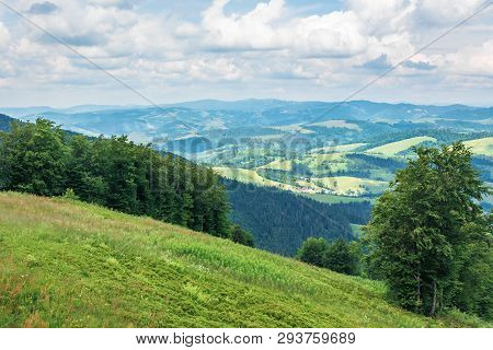 Beautiful Mountain Landscape In Summer. View From The Grassy Slope. Village On Rolling Hills Down In