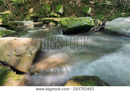 Forest Stream With Rocky Shore In Summer. Beautiful Nature Scenery. Moss On The Boulders. Long Expos