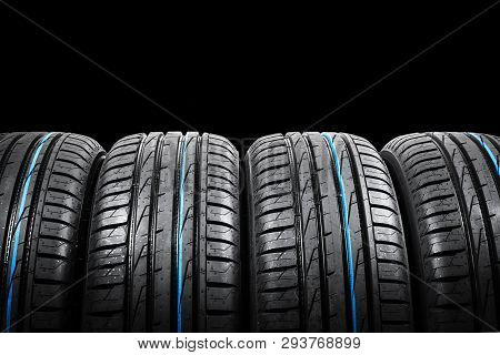 poster of Studio shot of a set of summer car tires on black background. Tire stack background. Car tyre protector close up. Black rubber tire. Brand new car tires. Close up black tyre profile. Car tires in a row