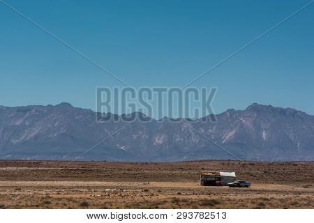 A lonely shack and car amidst the vast and dry Namibian landscape, with the Brandberg mountain in the background poster