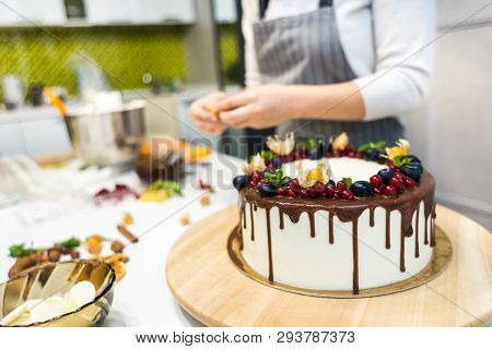 Confectioner Decorates With Berries A Biscuit Cake With White Cream And Chocolate. Cake Stands On A