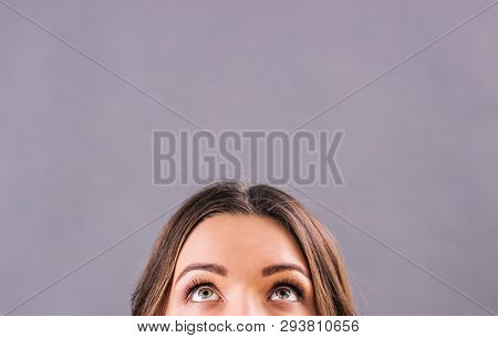 Closeup Beautiful Young Woman Looking Up On Blank Copy Space Isolated On Gray Background. Attractive