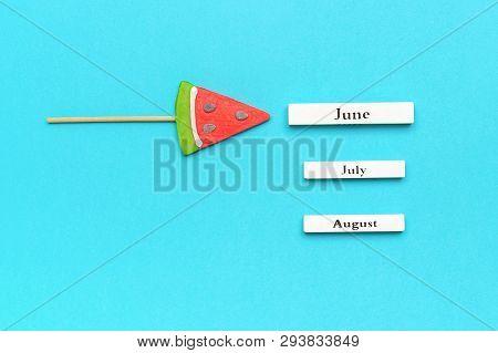Wooden Calendar Summer Months June, July, August And Watermelon Lollipop On Stick On Blue Background