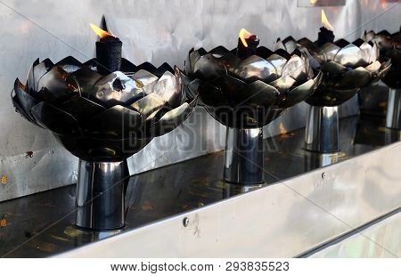Row of Gasoline Lamps or Oil Lamp in Lotus Shape In Thai Temple, Used to Worship, Pay Respect and Make Merit with The Buddha. poster