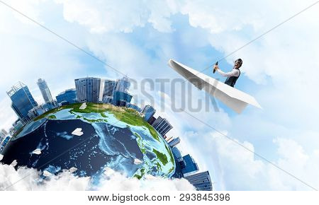 Pilot In Leather Helmet And Goggles Driving Paper Plane In Cloudy Blue Sky. Funny Man Flying In Smal