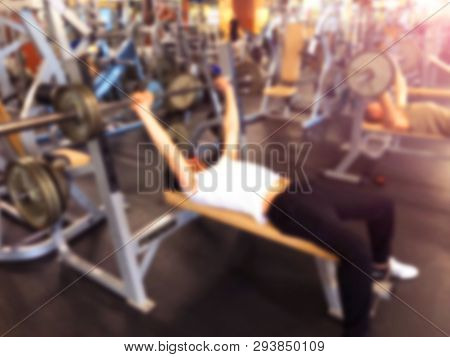 Blurred Background With Man Lifting Barbell Row At Gym. Blur Fitness Gym With People. Gym Equipment