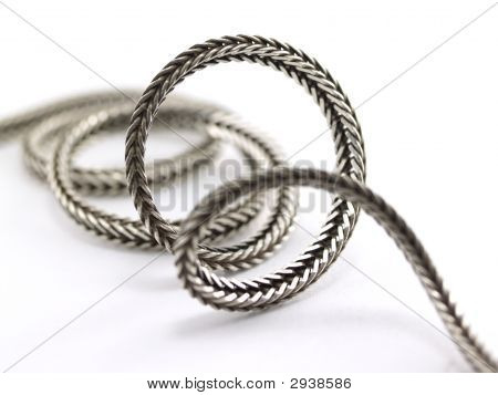 poster of Abstract photo of coiling silver chain on white background
