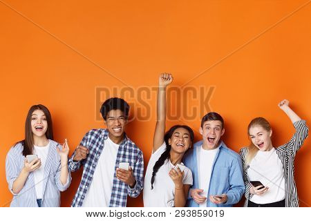 Excited Friends With Phones Screaming And Celebrating Success Over Orange Background, Copy Space