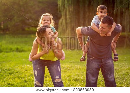 Happy Family -happy Family Piggyback Their Children And Have Fun Together In Park