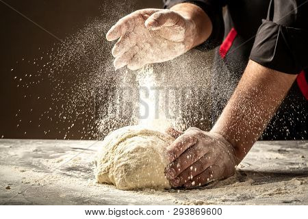 Chef Hands Cooking Dough On Dark Wooden Background. White Flour Flying Into Air. Food Concept.