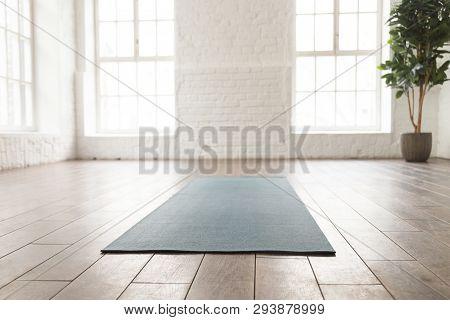 Empty Room In Yoga Studio, Unrolled Yoga Mat On Floor