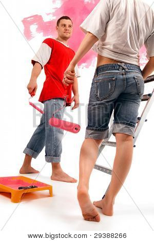 The forewoman standing against of young worker with roller
