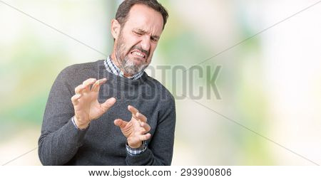Handsome middle age senior man wearing a sweater over isolated background disgusted expression, displeased and fearful doing disgust face because aversion reaction. With hands raised. Annoying concept