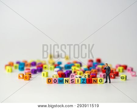 Miniature Figure Businessman In Dark Blue Suit Standing Backside Of Colorful Of Downsizing Alphabet
