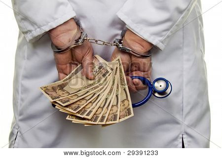 a doctor with japanese yen bank notes and handcuffs