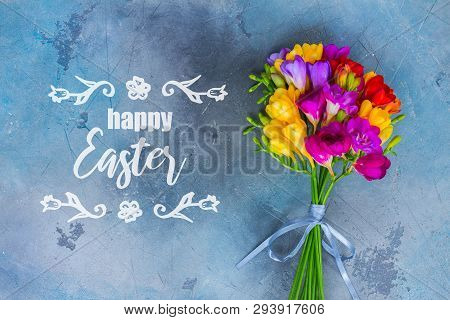 Posy Of Fresh Freesia Flowers On Gray Stone Background With Happy Easter Greetings