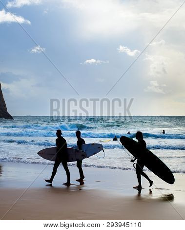 Group Of Surfers With Surfboards On The Beach. Algarve, Portugal