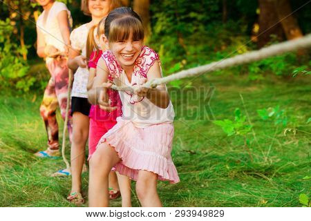Group Of Happy Children Playing Tug Of War Outside On Grass. Kids Pulling Rope At Park.