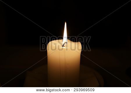 Lighted Single Candle. Selective Focus Of Candle. Candle Fire. Candle On A Dark Background