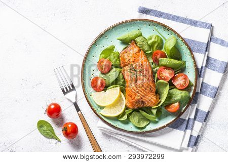 Keto Diet Food. Baked Salmon Fish Fillet With Fresh Salad From Spinach And Tomatoes. Top View On Whi