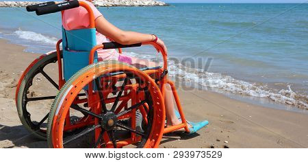 Summer Vacations Of A Little Girl On The Wheelchair On The Sandy Beach