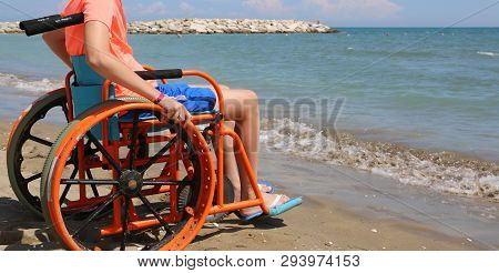 Young Boy On The Wheelchair On The Beach By The Sea In Summer