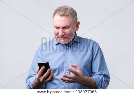 Annoyed Senior Man In Blue Shirt Looking At Mobile Phone