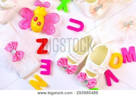 Baby Girl Wear Accessories And Toys On The Whiite Table