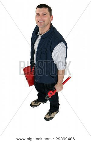 Tradesman holding a pipe wrench and a toolbox