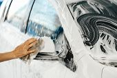 Woman hand washes a white car with a sponge and foam at a self-service car wash. poster