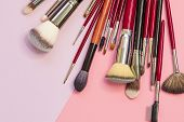 Set of different brushes for professional makeup, a multifunctional set of professional makeup artist. Brushes for application, shading. For eyes and Foundation, still life on a pink background poster