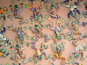 Multi-colored ceramic frogs hanging on a retailers wall in Taos New Mexico poster