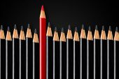 Business concept of disruption, leadership or think different; red pencil in front of row of black pencils standing out; minimal concept flat lay from above on black background poster