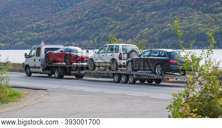 Car Carrier. Semi Truck - Transports Three Cars, Among Which Is A Sports Car, Very Expensive. Romani
