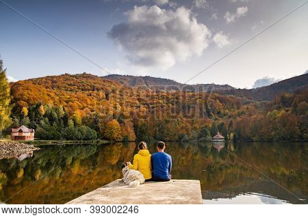 couple and dog sitting by beautiful autumn lake