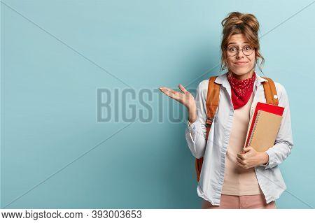 Doubtful Unaware Schoolgirl Raises Palm, Holds Spiral Notepad, Carries Rucksack, Gestures Over Blue